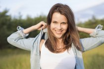 Portrait of woman with hands behind head in field — Stock Photo