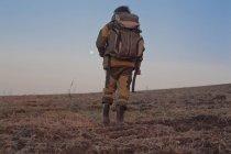 Homme marchant à travers le champ, vue arrière, vue basse — Photo de stock