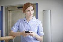 Krankenschwester mit Handy vor Krankenhauslift — Stockfoto