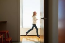 Girl running past doorway — Stock Photo