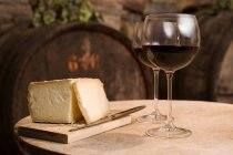 Cheese head and red wine glasses on table — Stock Photo