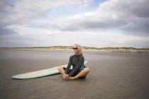 Старший женщина расслабляющий на песке, серфинг рядом с ней — стоковое фото