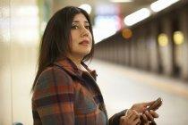 Femme d'affaires mature à la station de métro de la ville en utilisant un smartphone, Tokyo, Japon — Photo de stock