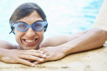 Portrait of young man wearing goggles in swimming pool — Stock Photo