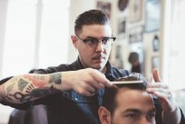 Barbeiro penteando de volta o cabelo do cliente na barbearia — Fotografia de Stock