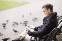 Jovem sentado no banco do Parque lendo jornal — Fotografia de Stock