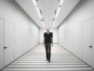 Man wearing black clothing walking through white corridor — Stock Photo