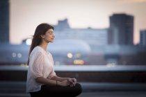 Vue de côté de femme méditant sur le toit — Photo de stock