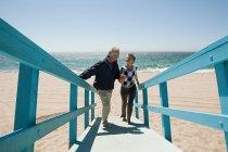 Mature couple walking on beach walkway — Stock Photo