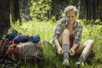 Teenage girl hiker putting on sock in forest, Red Lodge, Montana, USA — Stock Photo