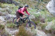 Молодая женщина катается на горном велосипеде по кустарнику — стоковое фото