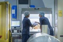 Рабочие проверяют материал на заводе по печати упаковки пищевых продуктов — стоковое фото