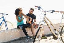 Пара сидить на стіні, узявши перерву, велосипеди біля них — стокове фото