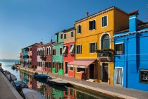 Colorful buildings above water canal in sunlight — Stock Photo