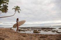 Giovane donna che tiene il surf sulla spiaggia — Foto stock