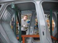 Lavoratore di ispezionare parti di automobili nella fabbrica di automobili — Foto stock
