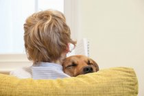 Garçon, lecture et câliner chien — Photo de stock