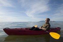 Side view of young man in kayak on water holding paddles, eyes closed, Great Salt Lake, Utah, USA — Stock Photo