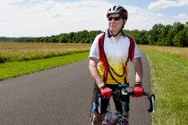 Старший чоловік велосипедів верхової їзди через сільську місцевість — стокове фото