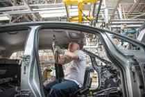 Arbeiter montiert Dachhimmel in Auto in Autofabrik — Stockfoto