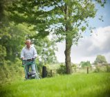 Gardener wearing ear protectors mowing lawn with lawn mower — Stock Photo