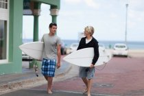 Teenage boys carrying surfboards, focus on foreground — Stock Photo