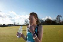 Menina água potável no campo — Fotografia de Stock