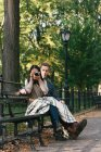 Mid adult woman sitting on park bench with boyfriend taking photographs on SLR camera — Stock Photo