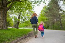 Rear view of mother and daughter holding hands walking down road through woods — Stock Photo