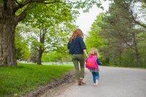 Задний вид матери и дочери, держащихся за руки, идущих по дороге через лес — стоковое фото