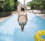 Woman jumping into swimming pool, Amagansett, New York, USA — Stock Photo