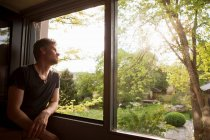 Man admiring landscape from window — Stock Photo