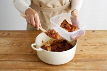Cropped image of Woman spooning meat into plastic container in kitchen — Stock Photo