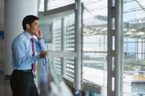 Empresário, falando no celular e no escritório — Fotografia de Stock