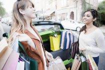 Mulheres carregando sacos de compras no carro — Fotografia de Stock