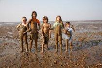 Crianças cobertas de lama na praia rochosa — Fotografia de Stock