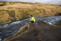 Male tourist crouching on riverbank, Skogafoss, Iceland — Stockfoto