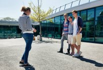 Friends walking together in courtyard — Stock Photo
