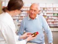 Le pharmacien parle au patient en magasin — Photo de stock