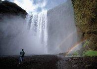 Excursionista admirar el arco iris en la cascada - foto de stock