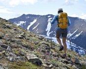 Female mountain climber walking uphill, rear view, Chugach State Park, Anchorage, Alaska, USA — Stock Photo
