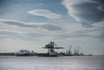 Cranes and ships at sea with clouds in sky — Stock Photo