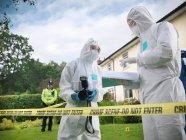 Cientistas forenses em discussão no local do crime, uma câmera de segurança, policial em segundo plano — Fotografia de Stock