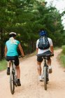 Couple mountain biking on dirt road — Stock Photo
