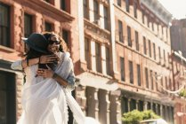 Two mid adult female friends hugging on city street — Stock Photo