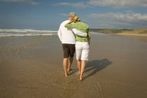 Rear view of mature couple walking on sandy beach — Stock Photo