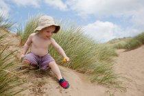 Ragazzo che gioca sulle dune di sabbia — Foto stock
