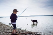 Boy fishing with dog in creek — Stock Photo