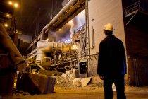 Worker walking in steel forge — Stock Photo