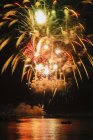 Fireworks exploding over water — Stock Photo